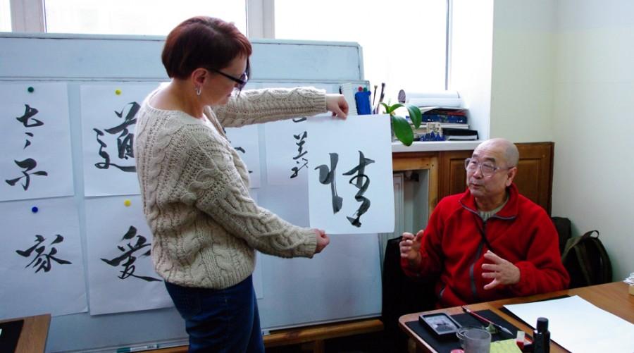 Мастер Му Юйчунь на занятии рассказывает о тонкостях каллиграфии. на фото: образцы работ мастера, написанные для учеников