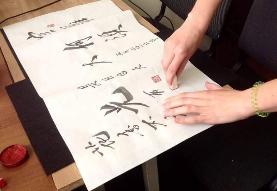 важный элемент в каллиграфической работе - печать-чжуань. На фото: коллективная работа занимающихся на курсах - заключительные штрихи в оформлении